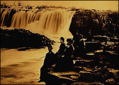 Historic photo of people sitting on rocks near falls.